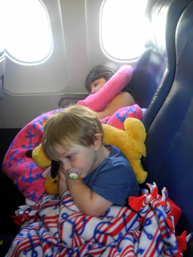 kids behaving resting on airplane with pillows