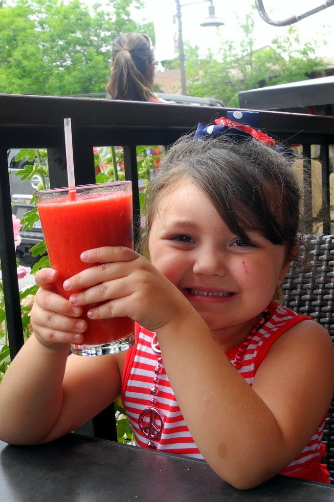 Daughter drinking smoothie on patio