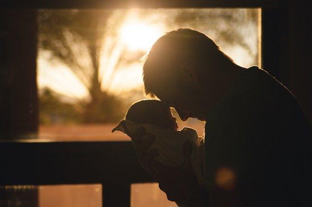 man holding baby lovingly