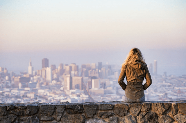 Woman solo traveler looking at city in the distance
