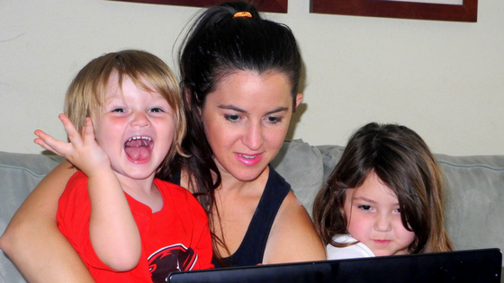 busy mom trying to work on computer with kids on lap